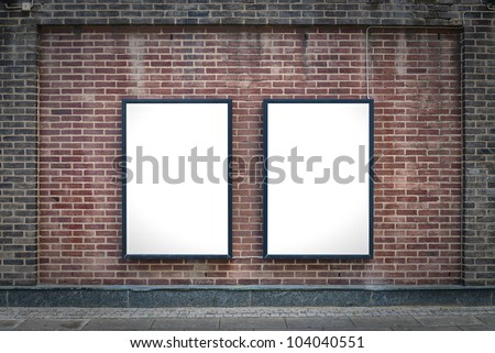 Two blank billboards attached to a buildings exterior brick wall. - stock photo
