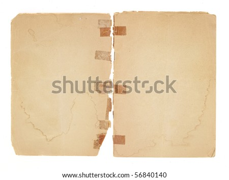 Two blank facing pages from an old pamphlet.  There is very old, yellowed tape on the broken binding. The paper is water stained, torn and yellowing with rough edges and dogeared corners. - stock photo
