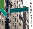 Two blank green street signs on a post at the intersection of two city streets. Insert your own words to easily customize the message. - stock photo