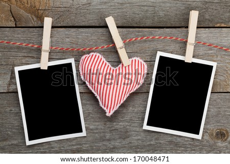 Two blank instant photos and red heart hanging. On wooden background - stock photo