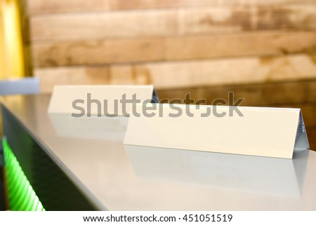 Two blank name tags on reception desk - stock photo