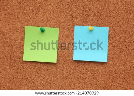 Two blank post-it notes on corkboard (bulletin board). - stock photo