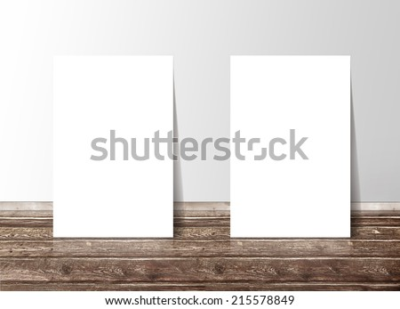 Two blank white paper template banners on the wooden floor against the wall - stock photo