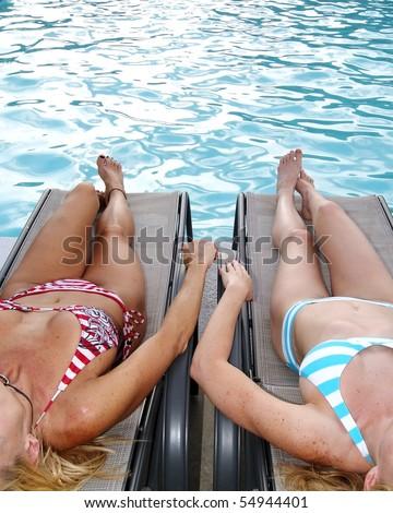 Two Blond Bikini Women Relaxing Poolside in Chairs - stock photo