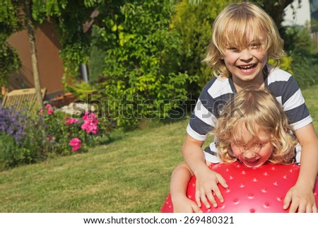 Two blond boys are playing with gymnastic ball at the garden - stock photo