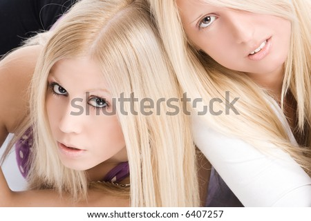 two blond girls, face to face, studio shot - stock photo