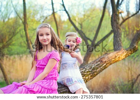 Two blond happy toddler sisters sitting on tree in spring green park in dresses care and brushing hair - stock photo