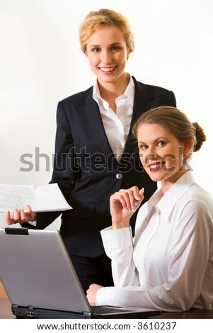 Two blond smiling women looking at the camera at the working table with opened lap top on it in the office