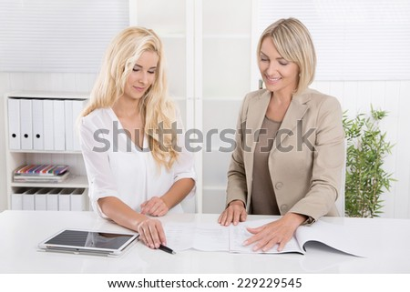 Two blond successful attractive businesswoman working in a team analyzing business papers. - stock photo