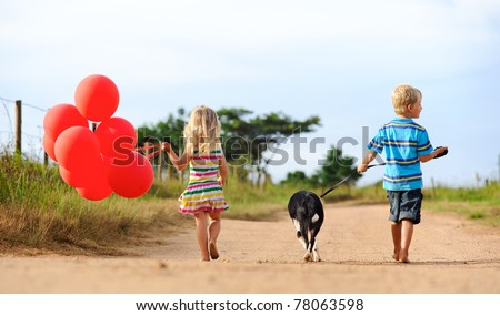 Two blonde children walking along a sandy path with red helium balloons and their puppy - stock photo