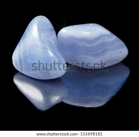 Two Blue Agate (sapphirine) stone close up  with reflection on black background - stock photo