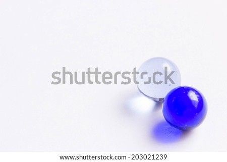 Two blue and clear glass marbles - Lower right - stock photo