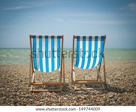 Two blue and white striped deck chairs on a pebble beach - stock photo