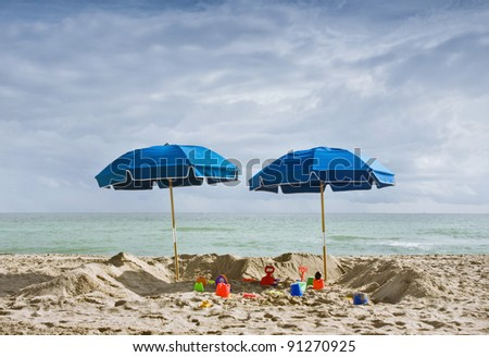 Two blue beach umbrellas and children's toys on the sand on a sunny beautiful summer day - stock photo