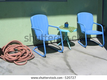 two blue chairs on a patio with a rolled-up red garden hose - stock photo