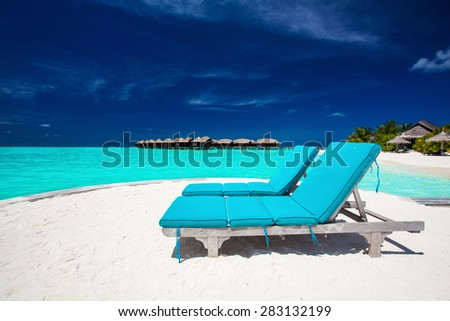 Two blue chairs on sandy island overlooking stunning tropical beach of Maldives - stock photo