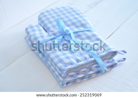 Two blue checkered oven gloves tied with a blue ribbon on an old white wooden table - stock photo