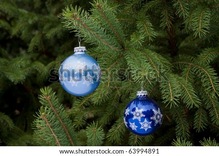 two blue christmas ornaments hanging on christmas tree, both are different shades of blue - stock photo