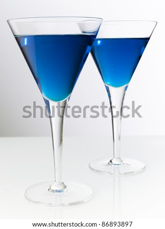 Two blue cocktails in classy cocktail glass.