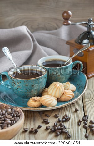Two blue cups of black coffee, biscuits and coffee grinder surrounded by linen cloth,  sugar pieces and coffee beans on old wooden table - stock photo