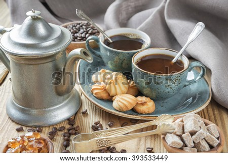 Two blue cups of black coffee, biscuits and coffee pot  surrounded by linen cloth, sugar pieces and coffee beans on old wooden table - stock photo