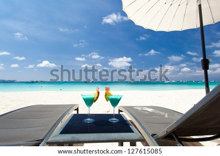 two Blue Curacao cocktails with slice of pineapple on white beach - stock photo