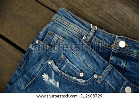 Two blue denim jean texture on wood background