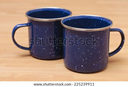 Two blue enamel mugs, the type that are used for camping - stock photo