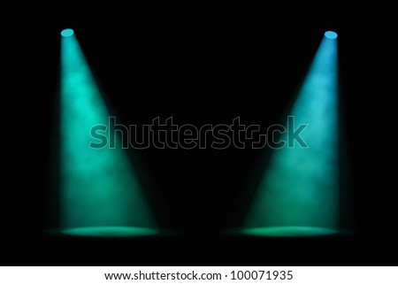 Two blue-green spotlights shining at a slight angle from either side of an empty stage with a foggy atmosphere and dark background