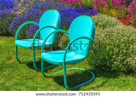 Two Blue Metal Retro Lawn Chairs Invitingly Sit On A Lawn In A Flower  Garden.
