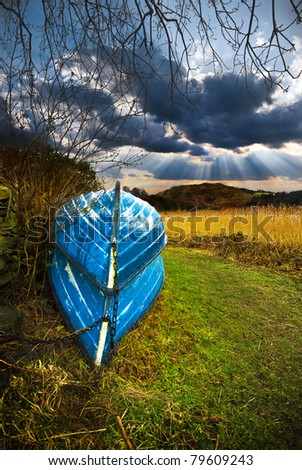 two blue upside down rowboats or rowing boats alongside a lake in the english lake district of cumbria with a spectacular evening sky beyond the mountain - stock photo