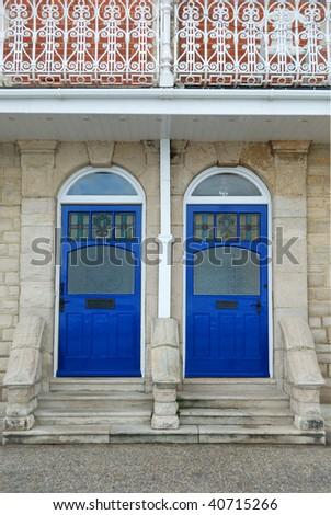 Two blue wooden doors mirroring one another. - stock photo