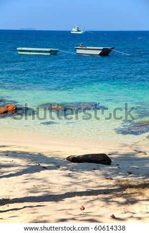 Two boat and fisherman fish park in the bay near island beach - stock photo