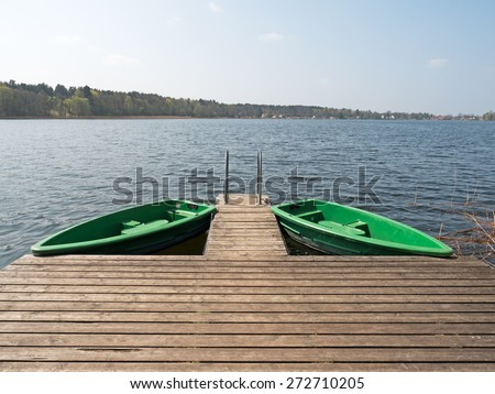 two boats at the dock on a lake - stock photo