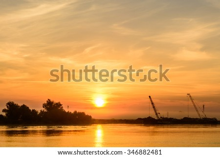 Two boats docking early in the morning near the pier. Horizontal view of a couple of boats loading up cargo in a summer morning over a sun rise sky on background. - stock photo