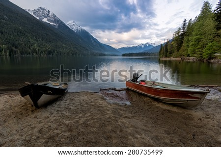 Two boats on sandy lake shore with distant mountains - stock photo