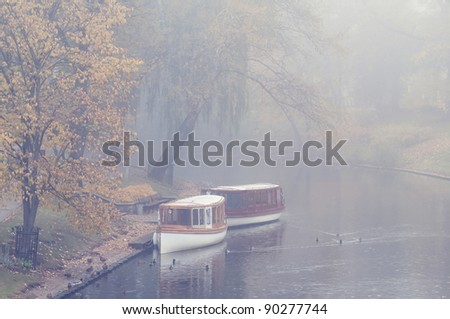 Two boats on the canal in the early foggy morning in Riga - stock photo