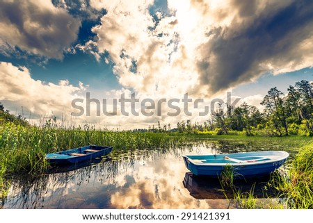Two boats on the lake in the woods. Image in the yellow-blue toning - stock photo