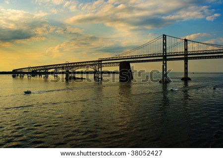 Two boats pass under Maryland's Chesapeake Bay Bridges as sunset approaches - stock photo
