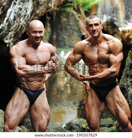 Two bodybuilders posing outdoors - stock photo
