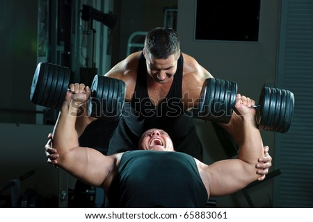 Two bodybuilders training in gym - stock photo