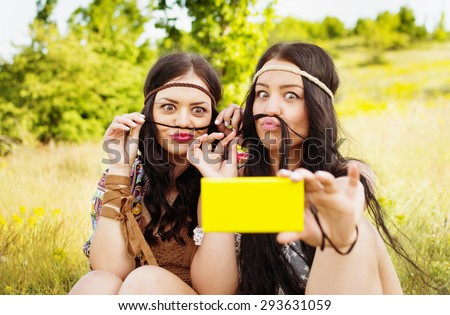 Two boho girls with long black hair making mustache taking a selfie in park on sunny summer day. Two modern young woman in hippie outfit taking self portrait. Horizontal, mild retouch, vibrant colors. - stock photo