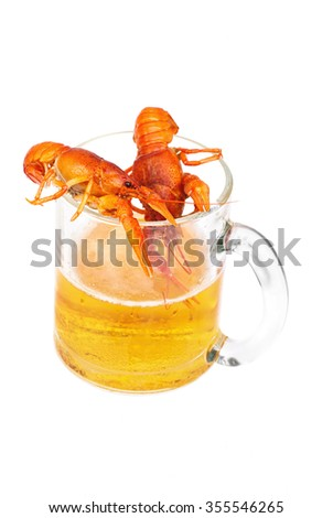 Two boiled red lobsters is lying on the glasses of fresh beer