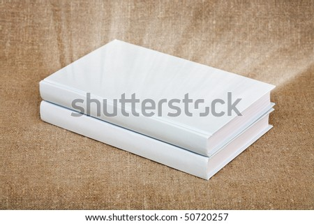 Two books in a white cover on the background of the old canvas - stock photo