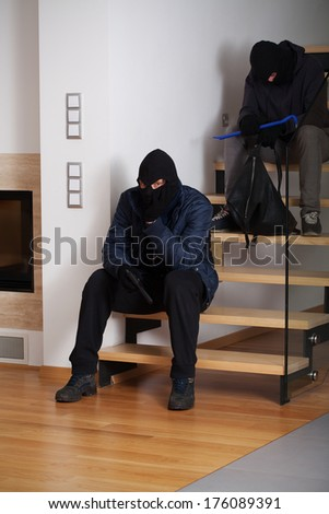 Two bored and resigned burglars waiting sitting on the stairs - stock photo