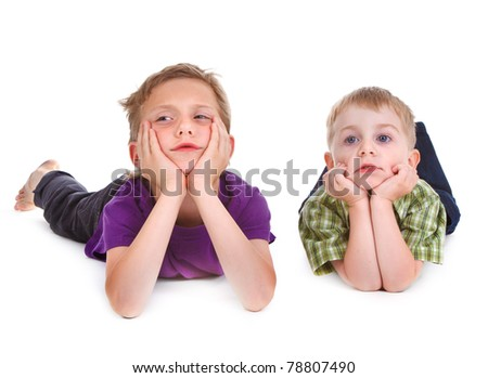 two bored kids lying on the white background - stock photo