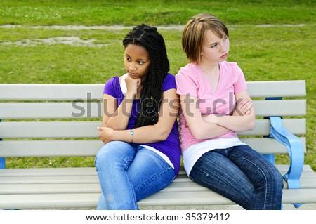 Two bored teenage girls sitting on bench - stock photo