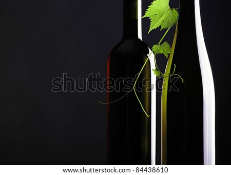 Two Bottle and one grape Leaves black background - stock photo