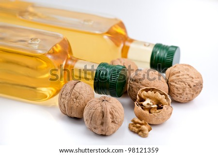 Two bottle of walnut oil and walnuts on the white background