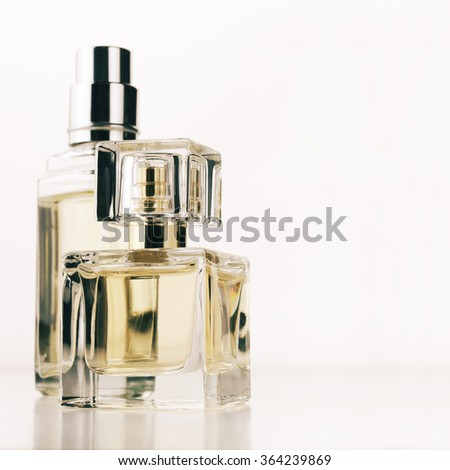 Two bottle of woman perfumes on white background. - stock photo